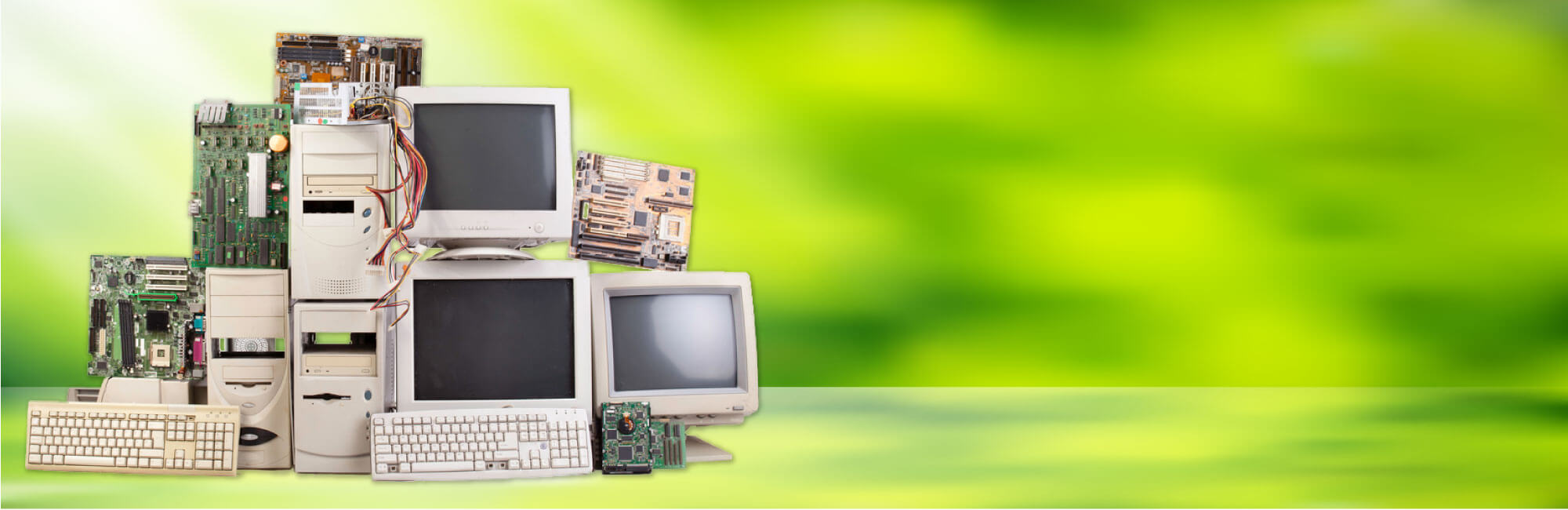 Pile of old computers, circut boards, and keyboards on a green background | Representing e-waste